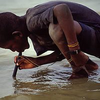 In a region of Mali still suffering from Guinea Worm, a young boy drinks from a lake, using filter that blocks the tiny disease-carrying parasites.