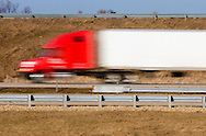 Modern trucks have sleek lines, as displayed by this tractor trailer rig speeding by an interstate on ramp.