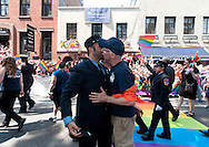 Two New York City Firemen kiss in front of the historic Stonewall Inn on Christopher Street during the 2016 Pride Parade in New York, NY on Sunday, June 26, 2016. Marchers and revelers acknowledged the recent fatal shooting at the Pulse nightclub in Orlando, FL and the historic Stonewall Inn in Greenwich Village being named a national monument.  © Chet Gordon • Photographer
