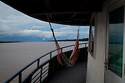 A lone hammock with the best views at the bow of the Avenger.  The Avenger III is a passenger ship making the twice a month journey from the frontier town of Tabatinga in the Tr&ecirc;s Fronteiras region of Northwestern Brazil, to the capital of the State of Amazonas, Manaus. It&rsquo;s also where the Rio Amazonas enters Brazil from its source in neighboring Peru. <br /> <br /> Carrying passengers and crew totaling almost 200 and small cargo, the ship meanders its way along the Rio Amazonas and Rio Solimoes for four days and three nights. Stopping at half a dozen or so makeshift ports en-route, the service provides a vial link for communities along the river to get products to the city and more importantly, in the absence of roads or airfields, provide a means for the sick to reach care in the city of Manaus.<br /> <br /> For those not fortunate to be accommodated in one of the two or three cabins available, home is space found for a self supplied hammock amongst the kaleidoscopic web of coloured fabrics. <br /> <br /> By the second day, negotiating a stroll from port to starboard can seem more like negotiating an assault course of tangled ropes and personal baggage deliberately piled high to protect ones personal space.<br /> <br /> Food served three times daily is adequate, a staple of soups, chicken, rice and noodles. An &lsquo;entertainment&rsquo; deck on the top floor provides ample opportunity to be social engaging in card and board games with beer swilling, chain smoking locals.