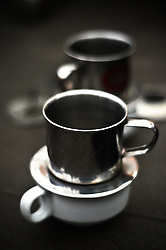 Two white coffee cups with metal filter on top of them.