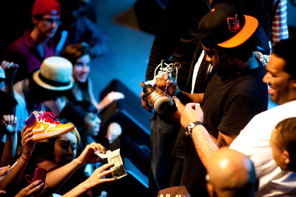 Wale, signing Nike boots and dollar bills.