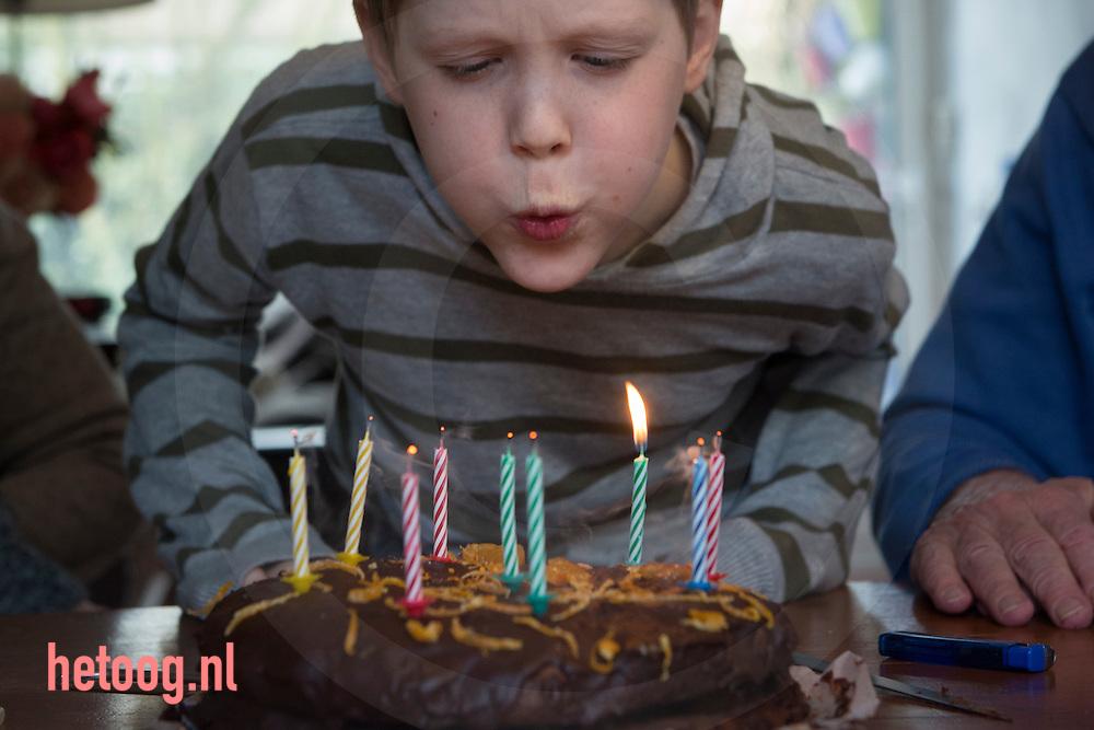 nederland, enschede, jarige blaast kaarsjes uit op chocoladetaart