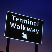 Overhead signpost to terminal walkway with arrow pointing right at sunset.