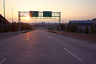 The sun sets behind the signs pointing traffic north or south on Riley Road from the steep downgrade off of the massive structure of Cline Avenue over the Calumet River channel.