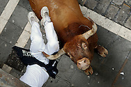 PAMPLONA, SPAIN - JULY 14: A Miura's fighting bull horns a runner at Calle Estafeta during the ninth day of the San Fermin Running Of The Bulls festival on July 14, 2014 in Pamplona, Spain. The annual Fiesta de San Fermin, made famous by the 1926 novel of US writer Ernest Hemingway 'The Sun Also Rises', involves the running of the bulls through the historic heart of Pamplona. (Photo by Pablo Blazquez Dominguez/Getty Images)