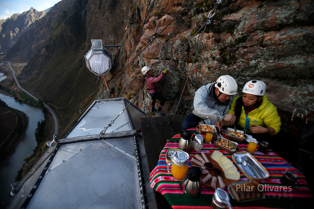Guests have breakfast as another guest climb to gather at the Skylodge Adventure Suites in the Sacred Valley in Cuzco, Peru, August 14, 2015. The Skylodge is composed by three capsule suites hanging at the top of the 1300 feet mountain with a 300 degree view of the Valley. To sleep at Skylodge, people must climb 400 meters of Via Ferrata path and to leave the hotel people go down  a trail through ziplines. REUTERS/Pilar Olivares