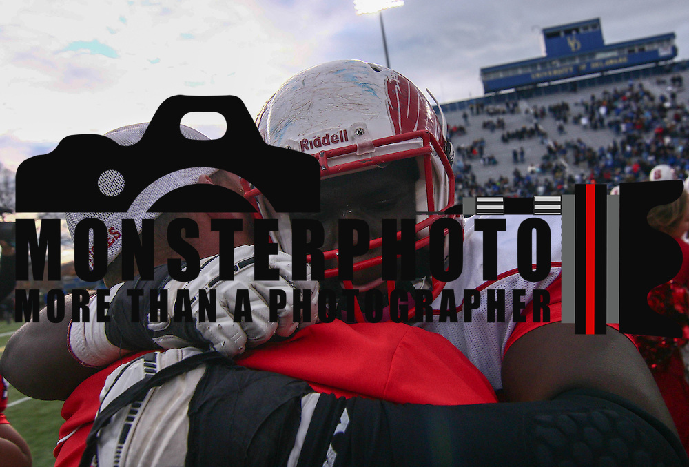 Smyrna Defensive linemen Jerren Carter (77) hugs a coach after winning the DIAA division one Football Championship game between Top-seeded Middletown (11-0) and second-seeded Smyrna (11-0) Saturday, Dec. 03, 2016 at Delaware Stadium in Newark.