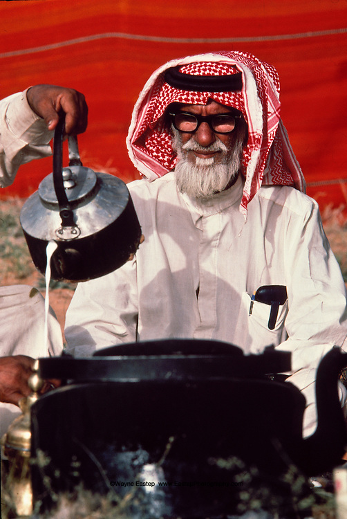 Mohammed bin salem Al Murrah being served hot camels milk with tea at breakfast, Dahana Sands, Saudi Arabia