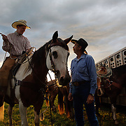 Young cowboy Wyatt Flattery, left, gets advise from Kenny Waterhouse before a cattle roundup where calves were roped, branded and vaccinated on the Bar B ranch near Albia, Iowa.  Owner Catherine Bay hires local workers with a bent for western flair, to help in the bi-annual task.