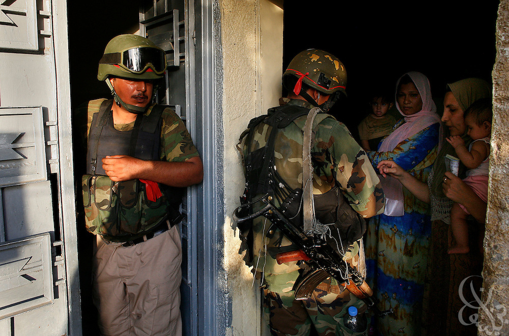 Iraqi National policemen speak with residents of an Iraqi household August 09, 2006 as part of a joint Iraqi Police and U.S. Army operation in the Doura district of Baghdad, Iraq.