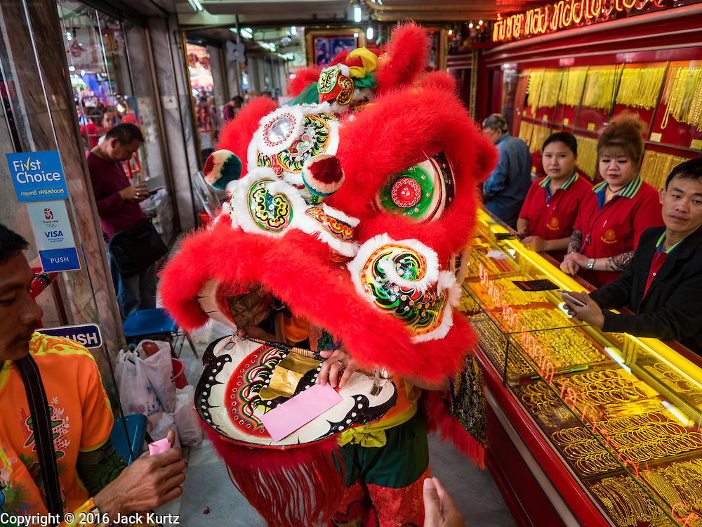 """08 FEBRUARY 2016 - BANGKOK, THAILAND:  Lion dancers perform inside a gold shop for Chinese New Year on Yaowarat Road in Bangkok's Chinatown district, during the celebration of the Lunar New Year. Chinese New Year is also called Lunar New Year or Tet (in Vietnamese communities). This year is the """"Year of the Monkey."""" Thailand has the largest overseas Chinese population in the world; about 14 percent of Thais are of Chinese ancestry and some Chinese holidays, especially Chinese New Year, are widely celebrated in Thailand.      PHOTO BY JACK KURTZ"""