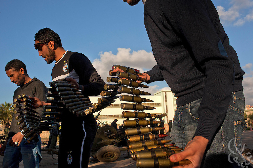Libyan men link belts of ammunition together for use by anti-aircraft weapons February 28, 2011 at a volunteer military camp in the eastern Libyan city of Benghazi. Opposition forces are on guard for airstrikes by forces of Libyan leader Col Muammar el-Qaddafi across eastern Libya after a reported airstrike on an opposition weapons deport near the city of Ajdabia. .Slug: Libya.Credit: Scott Nelson for the New York Times