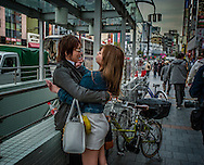 Contentious moment for couple just outside the o-hanami, cherry blossom viewing, festival.  In a country where couples are rarely demonstrative of affection, to express these emotions in public is almost unheard of.  Ueno, Tokyo, Japan.