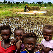 Sons and daugthers of local farmlabourers are portrayed in the rice-growing field of Bagré. Rice had increasingly become preferred by people living in the urban areas, as it was cheap and easy to cook, though overall it accounts for not more than 15 percent of grain consumption.