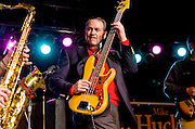 Republican presidential hopeful Mike Huckabee plays the bass guitar at a rally in West Des Moines, Iowa.