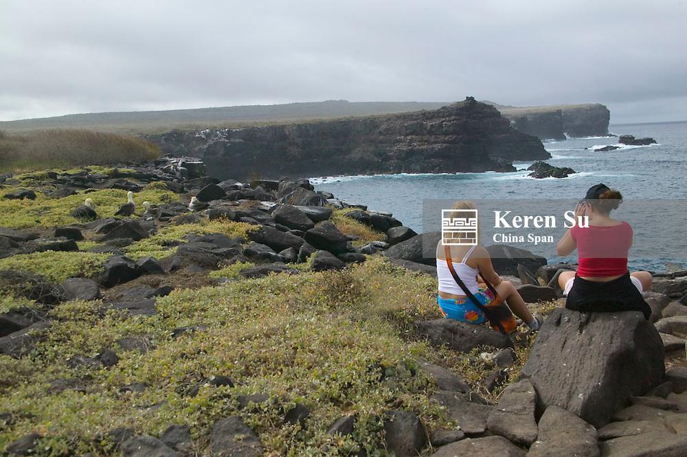 Tourists sitting on Galapagos Island with Marine Iguanas, Ecuador