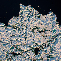 Canada, Nunavut Territory, Repulse Bay, Aerial view of melting icebergs floating in Hudson Bay on summer evening