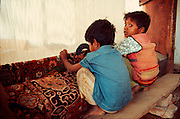 INDIA, RAJASTHAN, CRAFT small boys weaving carpets in a craft  shop in Jaipur, Rajasthan