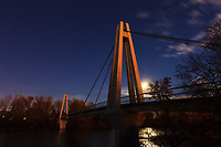 An almost full moon rises behind the pedestrian bridge between Riverbend and Sue Higgins Park (Southland Dog Park). The Moon came up just as the sun went down which allowed the <br /> <br /> &copy;2013, Sean Phillips<br /> http://www.RiverwoodPhotography.com