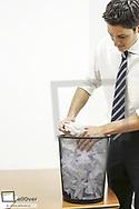 Junger Mann wuehlt in einem Papierkorb (model-released)