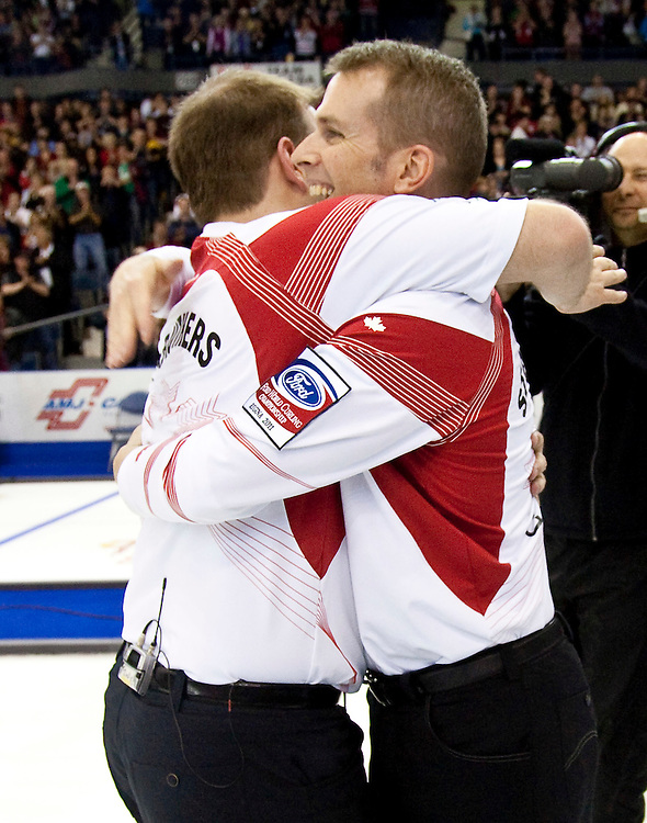Canadian skip Jeff Stoughton and second Reid Carruthers celebrate their victory over Scotland in the gold medal game at the Ford World Men's Curling Championships in Regina, Saskatchewan, April 10, 2011.<br /> AFP PHOTO/Geoff Robins