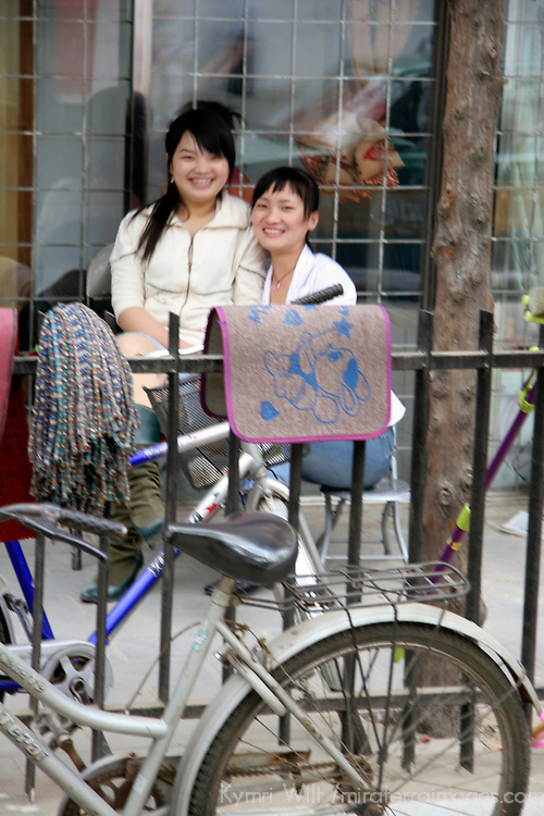 Asia, China, Beijing. Two girls smiing on busy Beijing street. (soft focus)