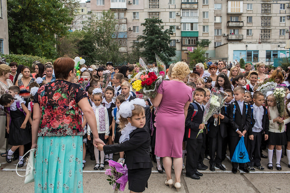 MARIUPOL, UKRAINE - SEPTEMBER 1, 2015: Students at School 68 arrive for the first day of the new school year in Mariupol, Ukraine. On January 24 of this year, shelling in the same neighborhood killed 31 people, all civilians, and while much recent fighting has been concentrated near Mariupol, a drop in ceasefire violations in the past few days has been credited to a desire to not interfere with the start of the new school year. CREDIT: Brendan Hoffman for The New York Times