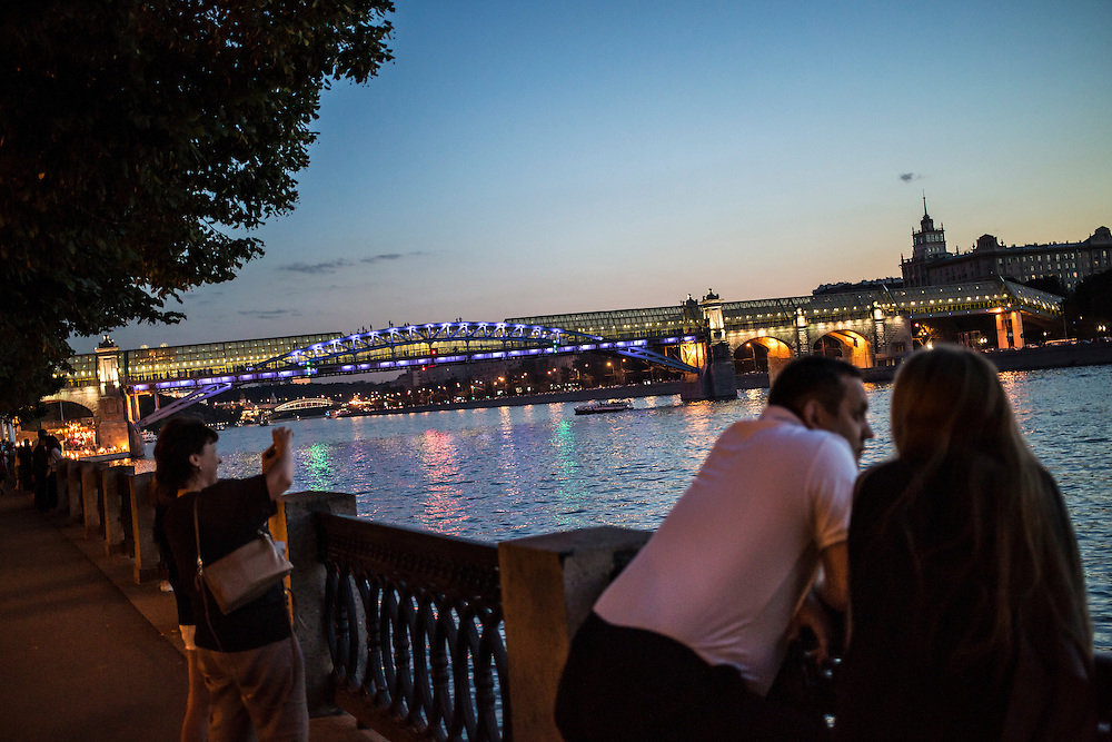 People linger by the Moscow River at sundown in Gorky Park on Saturday, August 17, 2013 in Moscow, Russia.