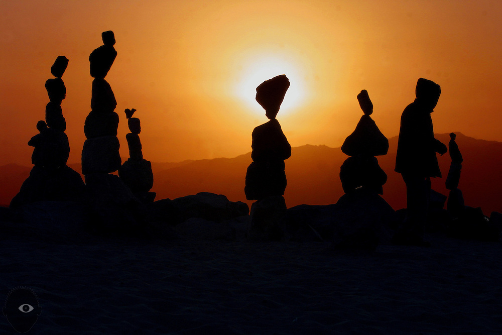 A rock stacking artist goes about his work as the sun sets on Venice Beach in California. He painstakingly worked for hours to balance rocks creating free-form sculptures.