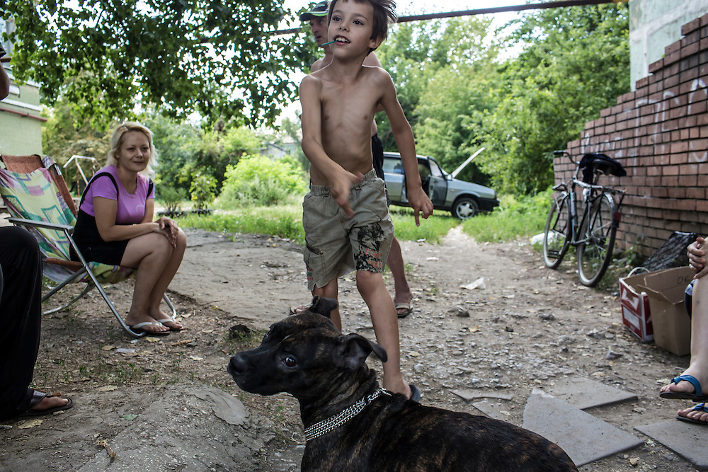 Residents of the Ploshchadka neighborhood, which has been heavily bombarded in recent days, gather outside a basement shelter on Wednesday, July 30, 2014 in Donetsk, Ukraine.