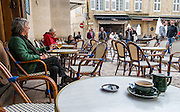 This woman lit her cigarette, sat down with a glass of wine and leisurely watched the tourists go by.  Lourmarin village, France.