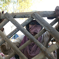 SIEM REAP, NOVEMBER-28: a worker stands at a fence during a break in Siem Reap, November 28, 2006, Cambodia.