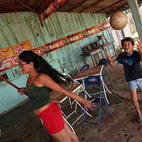 A woman plays pool in roadside bar as her young son plays wit a soccer ball in Marcelândia, in Mato Grosso state, in Brazil on April 6, 2008. (Photo/Scott Dalton)..
