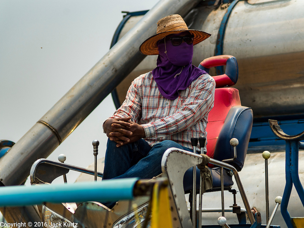 16 MARCH 2016 - BAN SONG, PRACHIN BURI, THAILAND: Workers on a mechanical rice harvester bring in the last of the 2015 rice crop in Prachin Buri province. Normally the farmers would plant a second crop of rice but they can't this year because their won't be enough water to irrigate the fields. The drought in Thailand is worsening and has spread to 14 provinces in the agricultural heartland of Thailand. Communities along the Bang Pakong River, which flows into the Gulf of Siam, have been especially hard hit since salt water has intruded into domestic water supplies as far upstream as Prachin Buri, about 100 miles from the mouth of the river at the Gulf of Siam. Water is being trucked to hospitals in the area because they can't use the salty water.    PHOTO BY JACK KURTZ