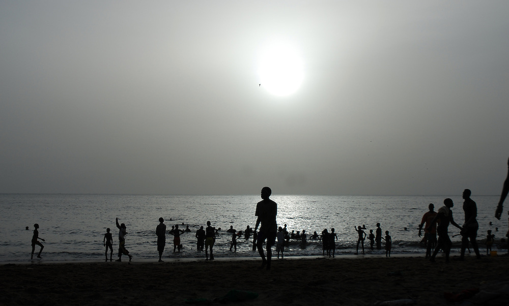 Children and youths swim in the sea off M'bour fishing port, Senegal.  In the late afternoon school children and youths head to the beach.  Thick cloud creates a grey haze through which the sun becomes a diffuse glow.
