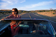 Fully Released, couple driving, 1962 Cadillac Convertible, lonesome Highway, Route 66, Near Grants, New Mexico, USA