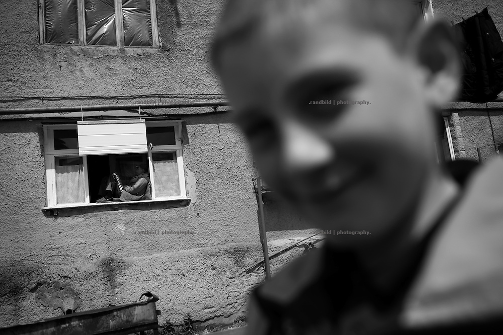 """A boy in a courtyard and a napping man in a window.This image is part of the photoproject """"The Twentieth Spring"""", a portrait of caucasian town Shushi 20 years after its so called """"Liberation"""" by armenian fighters. In its more than two centuries old history Shushi was ruled by different powers like armeniens, persians, russian or aseris. In 1991 a fierce battle for Karabakhs independence from Azerbaijan began. During the breakdown of Sowjet Union armenians didn´t want to stay within the Republic of Azerbaijan anymore. 1992 armenians manage to takeover """"ancient armenian Shushi"""" and pushed out remained aseris forces which had operate a rocket base there. Since then Shushi became an """"armenian town"""" again. Today, 20 yeras after statement of Karabakhs independence Shushi tries to find it´s opportunities for it´s future. The less populated town is still affected by devastation and ruins by it´s violent history. Life is mostly a daily struggle for the inhabitants to get expenses covered, caused by a lack of jobs and almost no perspective for a sustainable economic development. Shushi depends on donations by diaspora armenians. On the other hand those donations have made it possible to rebuild a cultural centre, recover new asphalt roads and other infrastructure. 20 years after Shushis fall into armenian hands Babies get born and people won´t never be under aseris rule again. The bloody early 1990´s civil war has moved into the trenches of the frontline 20 kilometer away from Shushi where it stuck since 1994. The karabakh conflict is still not solved and could turn to an open war every day. Nonetheless life goes on on the south caucasian rocky tip above mountainious region of Karabakh where Shushi enthrones ever since centuries."""