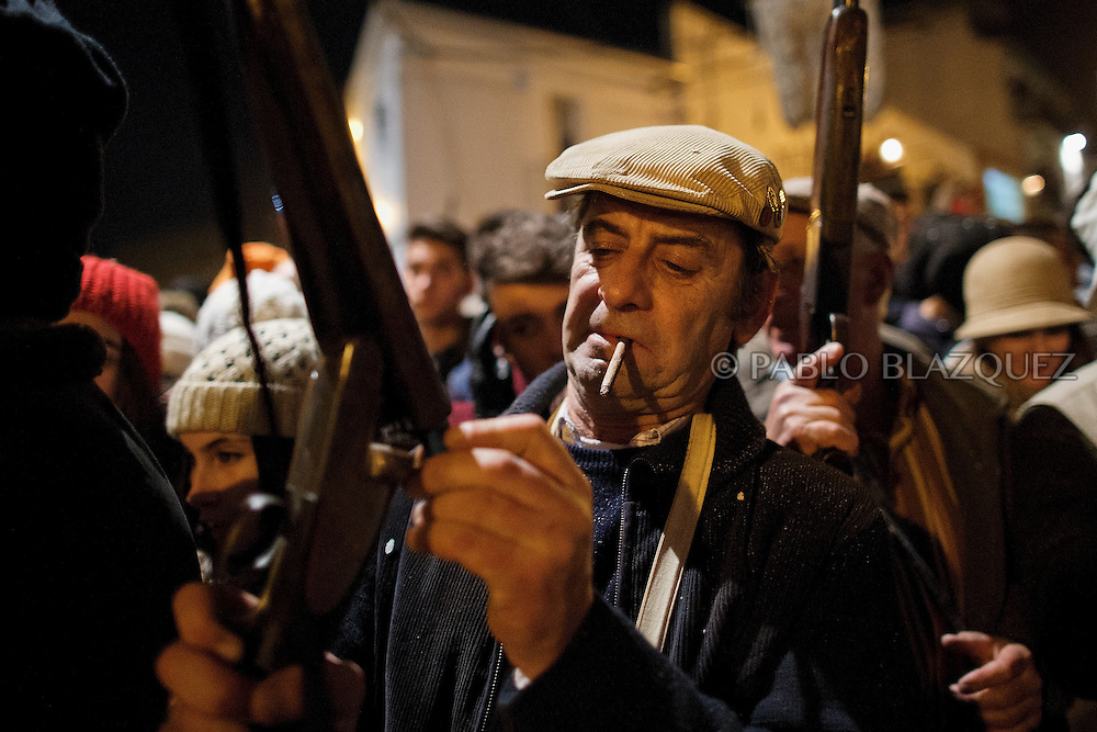 """A reveler loads a shotgun during the """"La Encamisa"""" Festival on December 7,  2014 in Torrejoncillo, Extremadura region, Spain. """"La Encamisa"""" is an ancient festival in honor of Immaculate Conception. Hundreds of horsemen wearing a white sheet gather outside the church in the main square. The procession starts when a banner with the image of Immaculate Conception is delivered to the horse rider steward and people cheer and shoot blanks. There are bonfires along the way where people gather to chat, eat traditional sweets and drink local wine. The origin of this tradition is unknown but it is believed the festival comes from a military event in which people from Torrejoncillo were involved. The war in Flanders in 1585, the Battle of Pavia or a legend of the siege suffered by city of Coria. (© Pablo Blazquez)"""