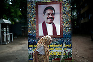A woman walks past a poster celebrating Sri Lanka's President Mahinda Rajapaksa in Colombo, Sri Lanka, July 4, 2009. With the end of the 26 war between the Sri Lankan government and the LTTE, security in the capital city remains on high alert.
