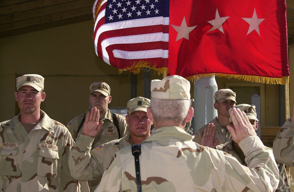 U.S. army soldiers take the oath of re-enlistment during a ceremony at Bagram Air Base July 4, 2002 in Afghanistan. Seven U.S. soldiers opted to re-enlist when their current enlistment expired while deployed on the ongoing Operation Enduring Freedom. The re-enlistment ceremony was one of a variety of activities scheduled for U.S. soldiers as part of the July 4th holiday.
