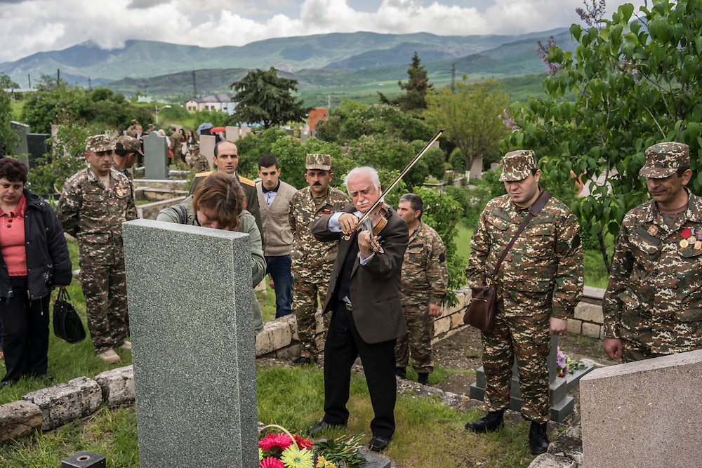 A woman weeps in mourning at the grave of a fighter killed in the 1990s war between Armenia and Azerbaijan as a man plays a somber song on the violin following a ceremony commemorating both the victory over Nazi Germany in the Second World War as well as the fall of the strategic town of Shushi to Armenian forces on Monday, May 9, 2016 in Stepanakert, Nagorno-Karabakh.