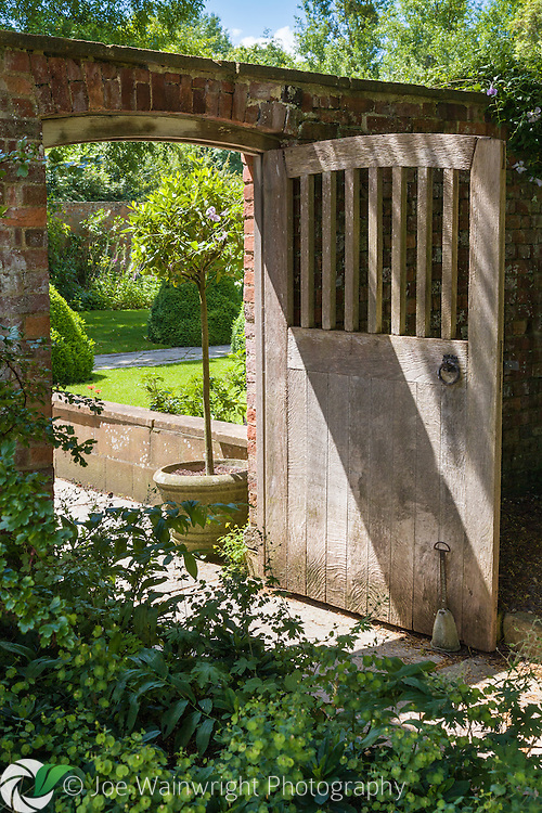 An open wooden gate at Tintinhull Garden, Somerset. Photographed in June
