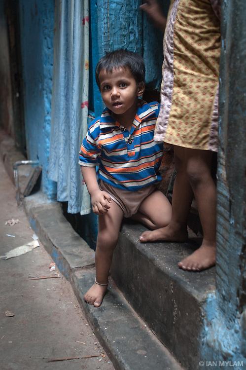 Young Boy on a Doorstep - Dharavi, Mumbai, India