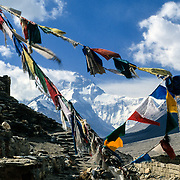 Prayer flags frame the massive North Face of Mount Everest from Rongbuk Monastery, Tibet, China.