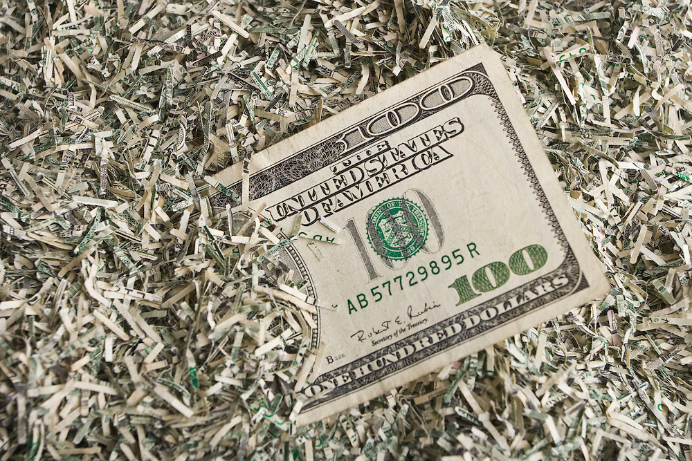Concept image using shredded United States currency and a $100 bill.