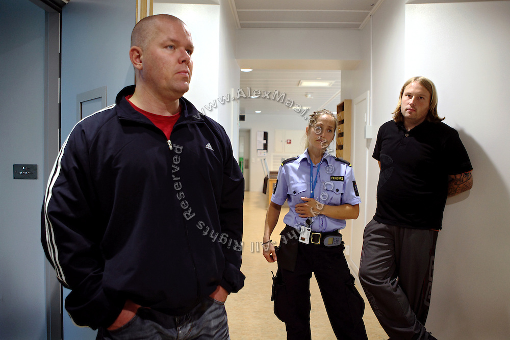 Two inmates (left and right) are standing by their bedrooms next to a woman guard (centre) inside the luxurious Halden Fengsel, (prison) near Oslo, Norway.