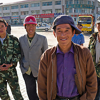Construction workers waiting for a pick-up job standing on the corner of a street in Xilinhot, Inner Mongolia, China.