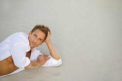 sexy man relaxing on wet sand