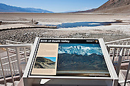 A lone tourist overlooking Badwater salt flat and water - Death Valley National Park, California